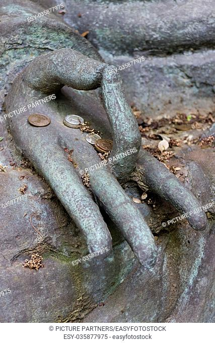 Tokyo, Japan - Hand with some Japanese coins of a Buddha statue in the garden of the Nezu museum