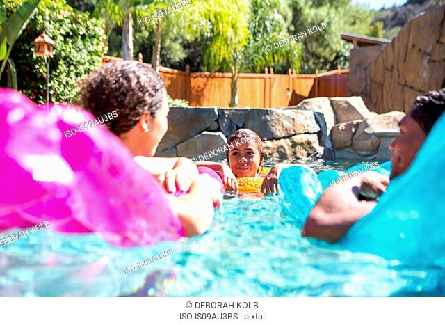 Family with girl in pool using inflatables talking