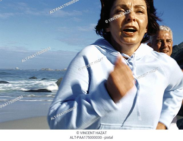 Mature couple running on beach, close-up