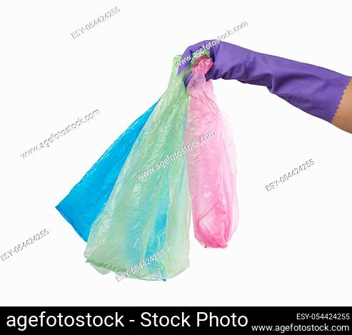 hand holds an empty green plastic bag on a white background, concept of rejection of plastic and the transition to eco-packaging
