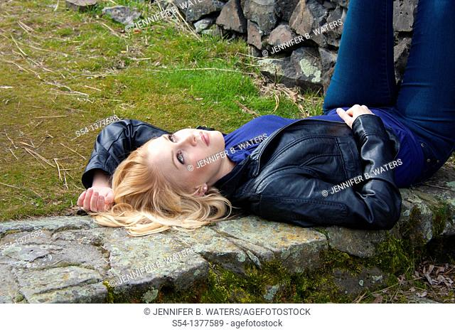 A young woman outdoors, laying on the ground