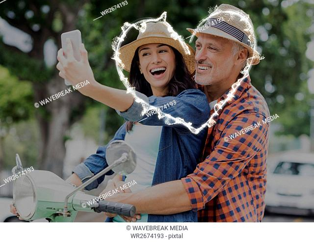 Happy couple taking selfie on scooter