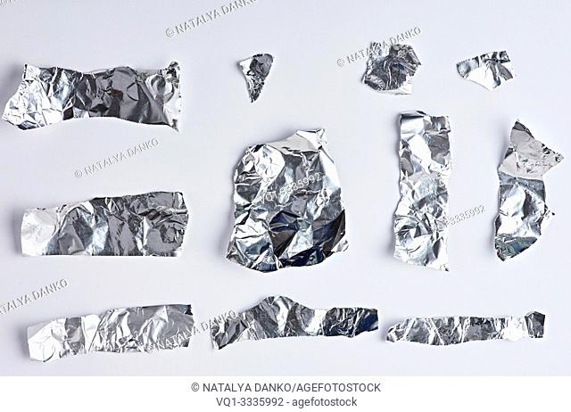 various pieces of silver foil on a white background, close up