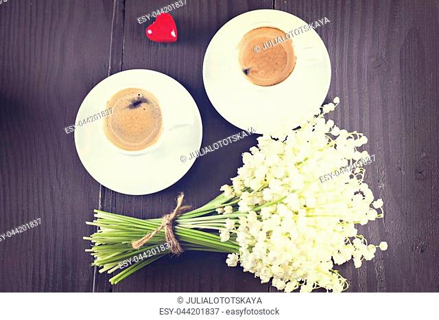 Two cups of coffee - espresso, heart and bouquet of flowers - lilies of the valley on black background. romantic breakfast for my birthday, Valentine's Day
