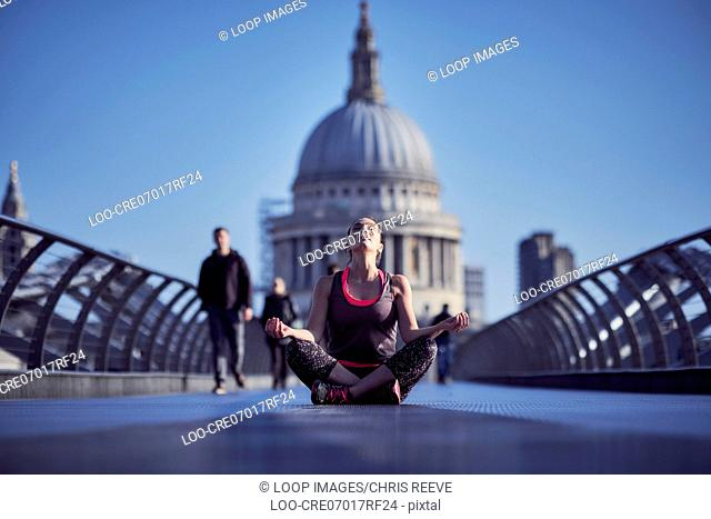 A woman meditating on the Millennium Bridge with St Paul's Cathedral in the background