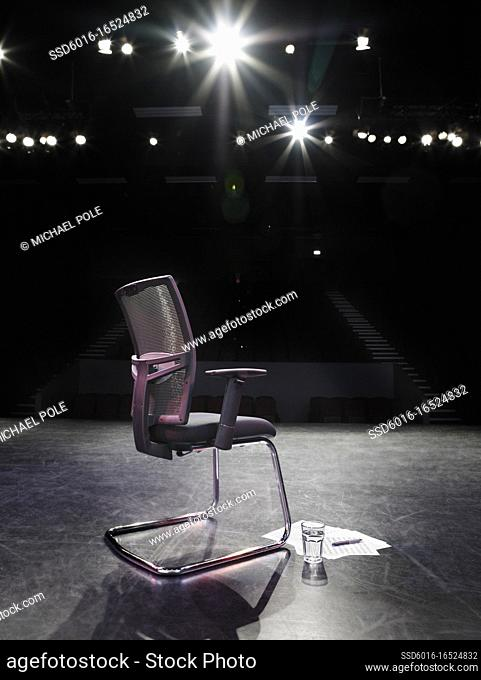 Back view of spotlit empty chair on stage with script and glass of water beside it and looking out to empty auditorium