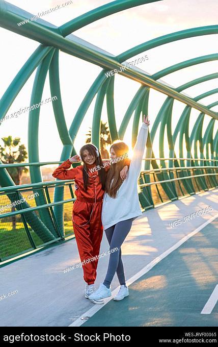 Carefree friends wearing headphones standing on bridge