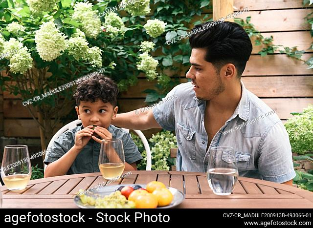 Father and son at decorated outdoor table with snacks and flowers
