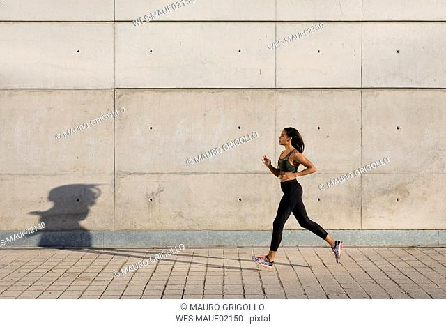 Young woman running along concrete wall in the city