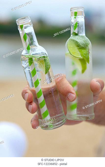 A man holding two bottles of Virgin Mojito