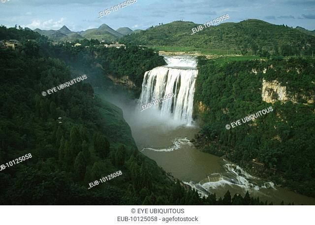 Huangguoshu Falls seen from a distance within lush green surrounding landscape