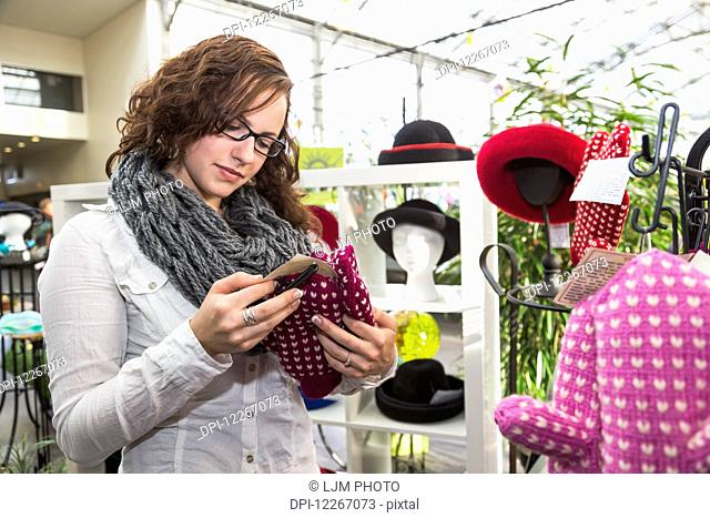 Young woman looking at knitted accessories in the mall; St. Albert, Alberta, Canada
