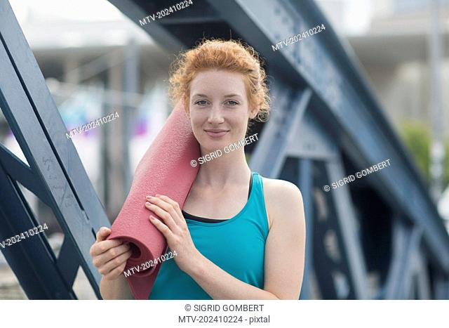 Portrait of a young woman standing with exercise mat in urban city, Freiburg im Breisgau, Baden-Württemberg, Germany