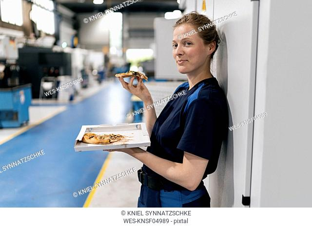 Woman working in high tech company, taking a break, eating pizza