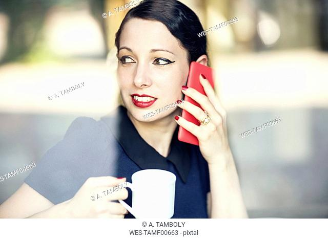 Young woman on cell phone in a cafe