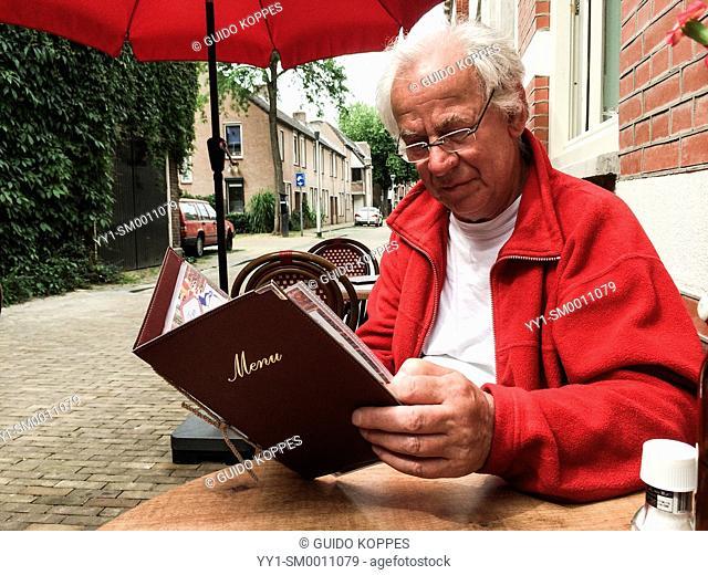 Tilburg, Netherlands. Elder man reading the menu of a cafe-restaurant prior to ordering lunch