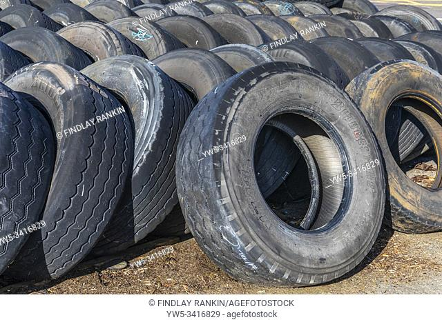 Used and worn lorry tyres stored at a garage, Scotland, UK