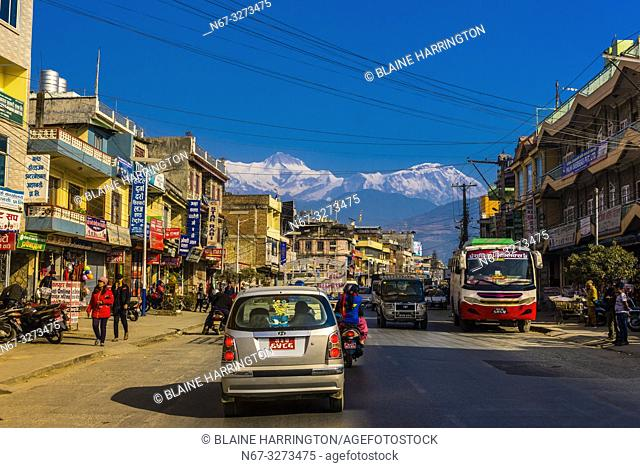 Street scene in Pokhara, Nepal with peaks of the Annapurna Massif of the Himalayas in the background