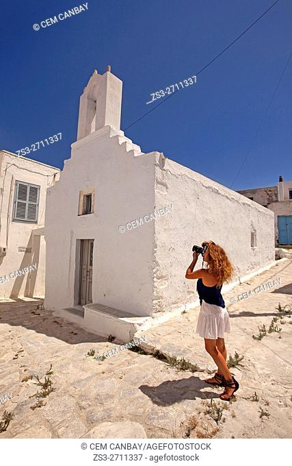 Woman taking photos in front of a whitewashed church in the old town Chora, Amorgos, Cyclades Islands, Greek Islands, Greece, Europe