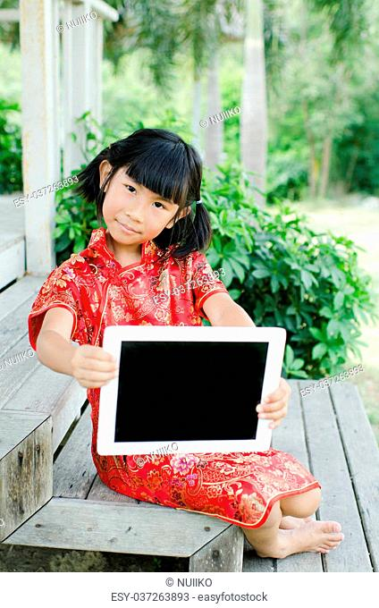 Asian child in traditional Chinese cheongsam showing tablet