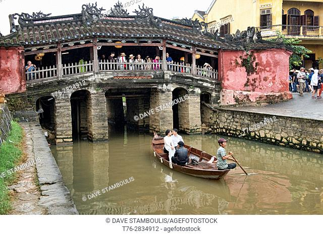 Newlywed couple in a rowboat at the Japanese Bridge, historic old district, Hoi An, Vietnam