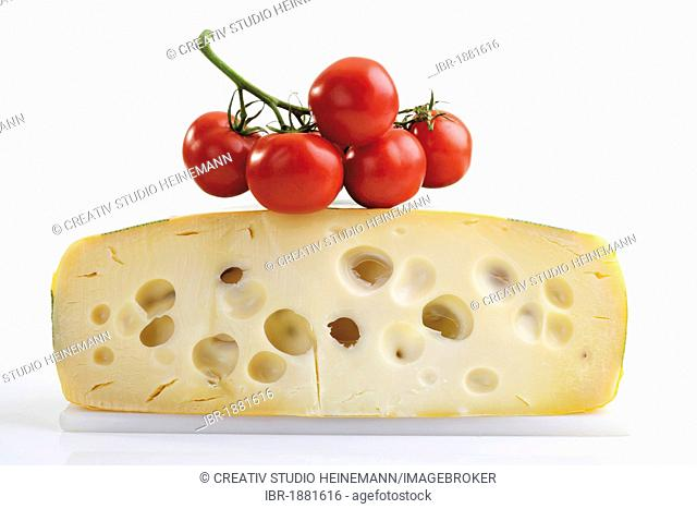 Half of a Leerdamer cheese wheel with tomatoes