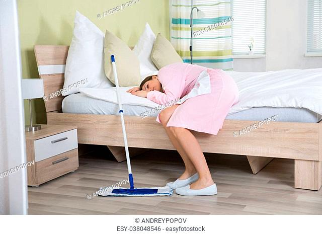 Tired Young Female Housekeeper Lying On Bed In Hotel Room
