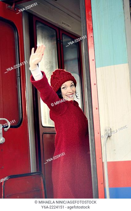 Woman on train waving goodbye