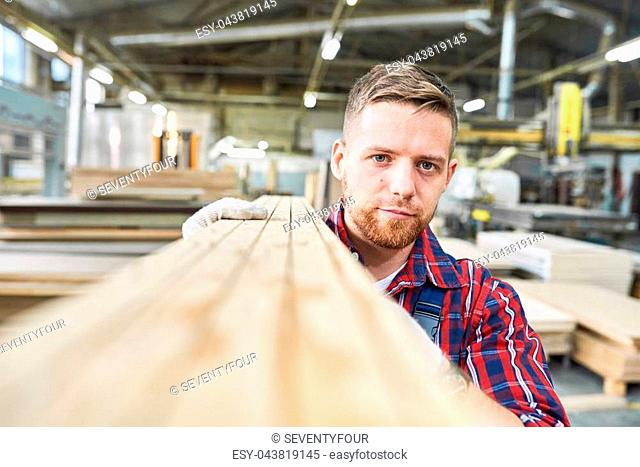 Head and shoulders portrait of handsome young factory worker looking at camera while carrying long wooden board moving material in workshop, copy space