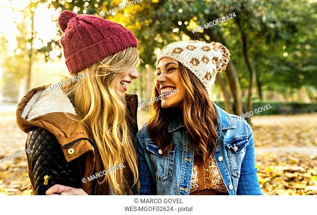 Two smiling young women wearing wooly hats in a park in autumn