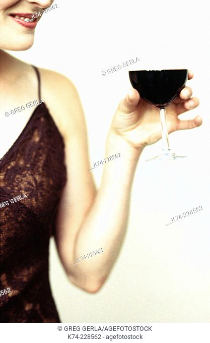 close up image of woman holding glass of red wine