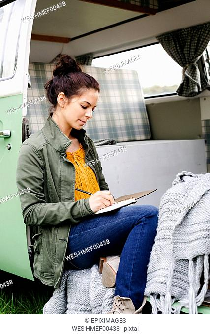 Young woman sitting in her camper, writing in a notebook