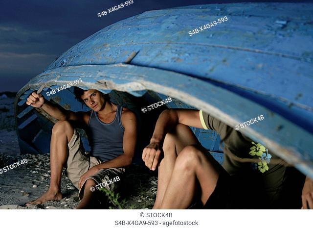 Two men sitting underneath a boat