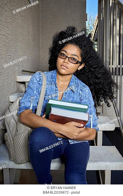 Serious Mixed Race teenage girl sitting on staircase holding books