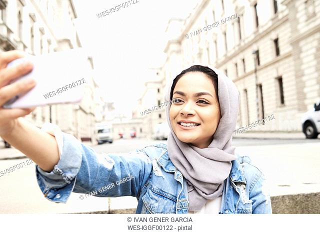 UK, England, London, young woman wearing hijab taking a selfie in the city