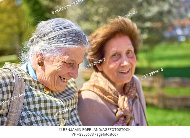 Happy two senior woman enjoying togetherness in park, Bavaria, Germany