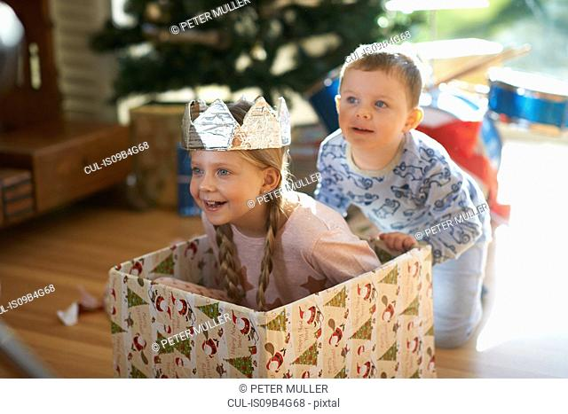 Boy pushing sister in cardboard box at christmas