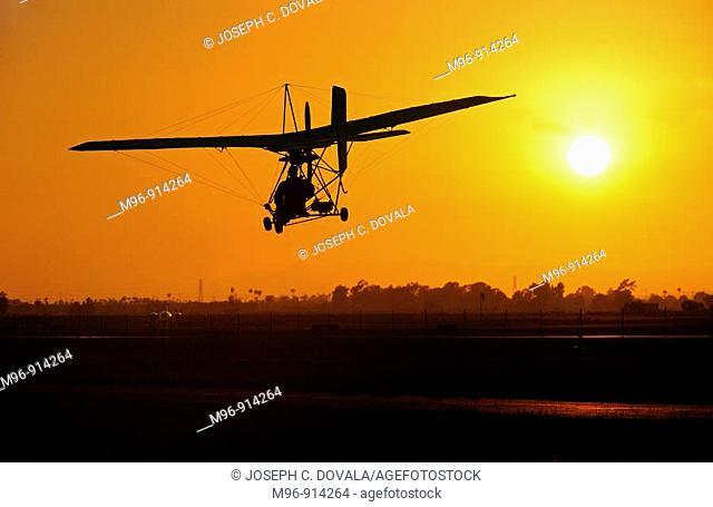 Single seat ultralight coming in for landing at sunset, Camarillo Airport, Camarillo, California, USA