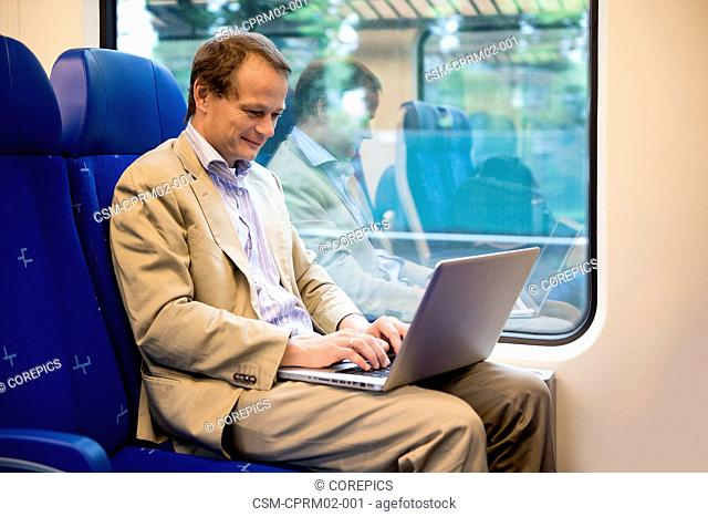 Businessman, travelling with a laptop on his lap in a train, commuting to and from work