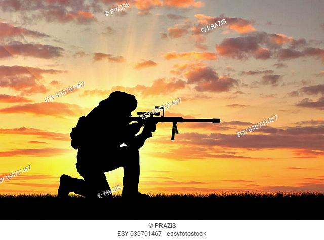 Concept of terrorism. Silhouette of a terrorist with a rifle on a background of a sunset