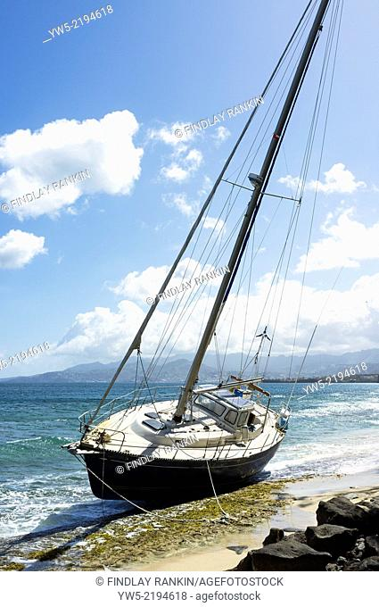 Yacht washed ashore and onto rocks at Pink Gin Bay, near St George, Grenada, West Indies