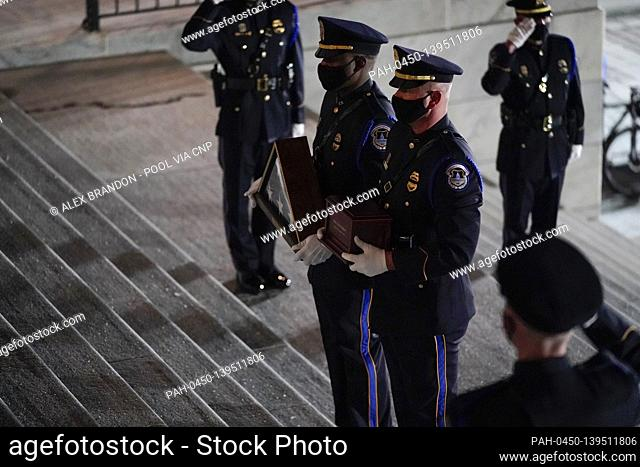 An honor guard carries an urn with the cremated remains of U.S. Capitol Police officer Brian Sicknick and folded flag up the steps of the U