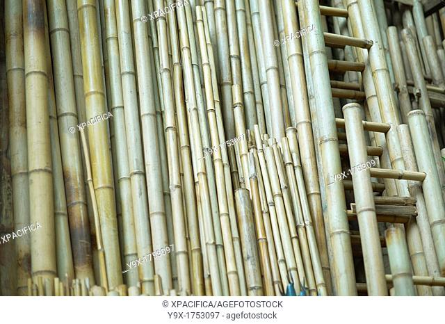 A bamboo store with different size bamboos lined up against the building