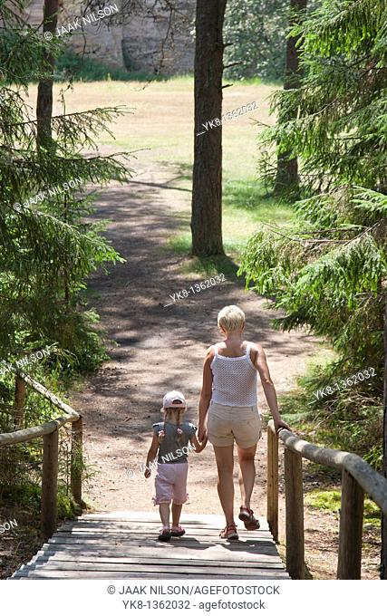 Mother and Young Girl Walking on Boardwalk in Forest Holding Hands, Põlva County, Estonia