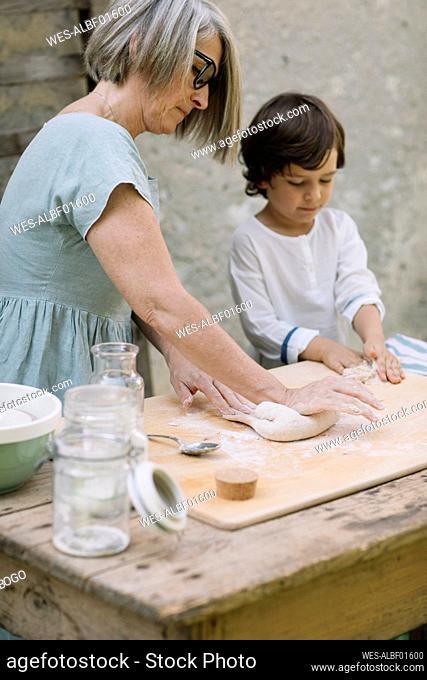 Grandmother with grandson preparing dough at back yard