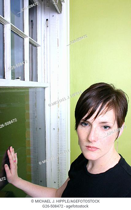 Portrait of young woman against lime green wall