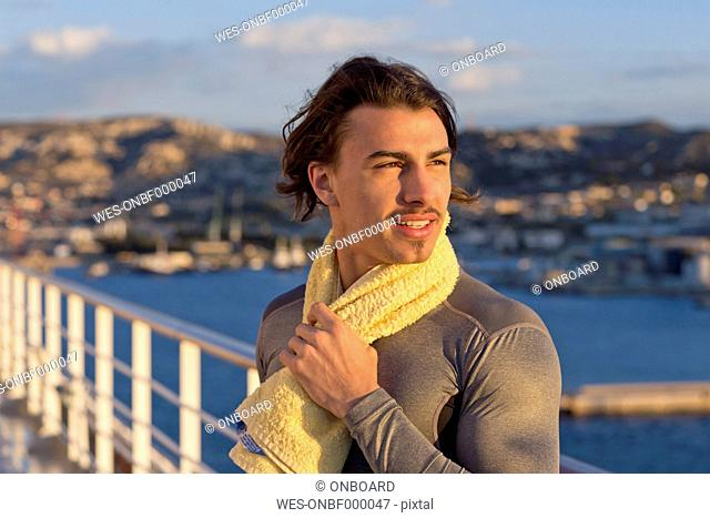 Portrait of young man with towel standing on deck of a cruise ship