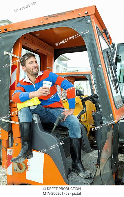 Construction worker sitting in excavator, drinking coffee