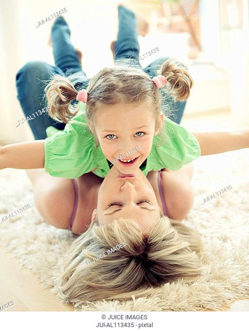 Mother lying on floor holding up daughter