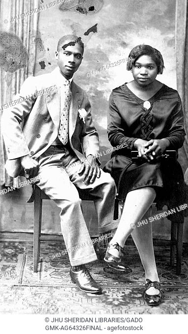 Young African American couple, a man and a woman seated together on a bench, the man wearing a suit, the woman wearing a dress and patent leather shoes, 1915